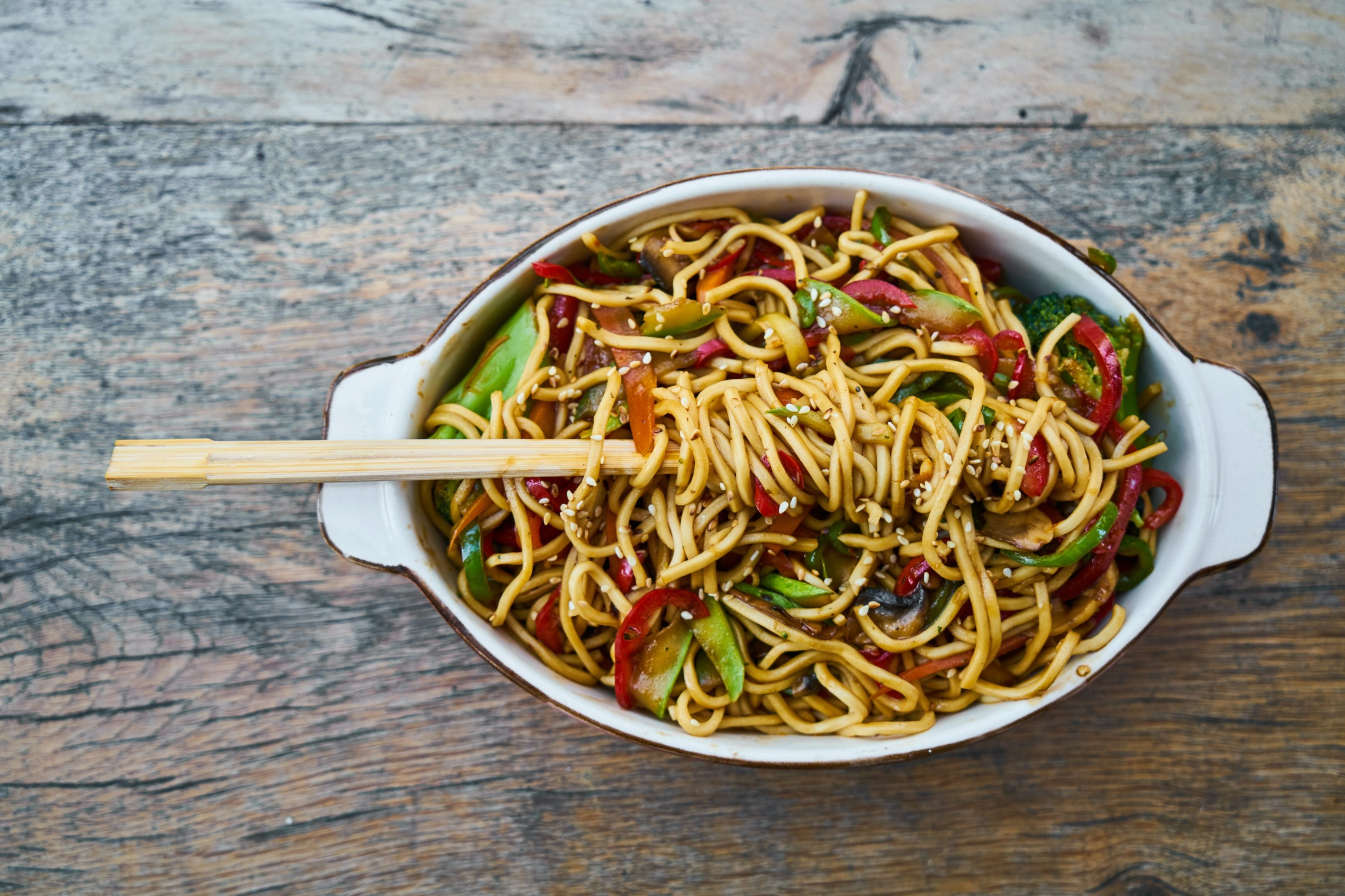 Stir Fried Noodles in a plate with a big wood spoon