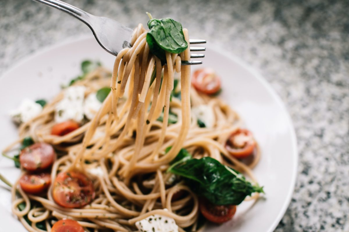 caprese pasta on a white plate with mozarella and tomatoes