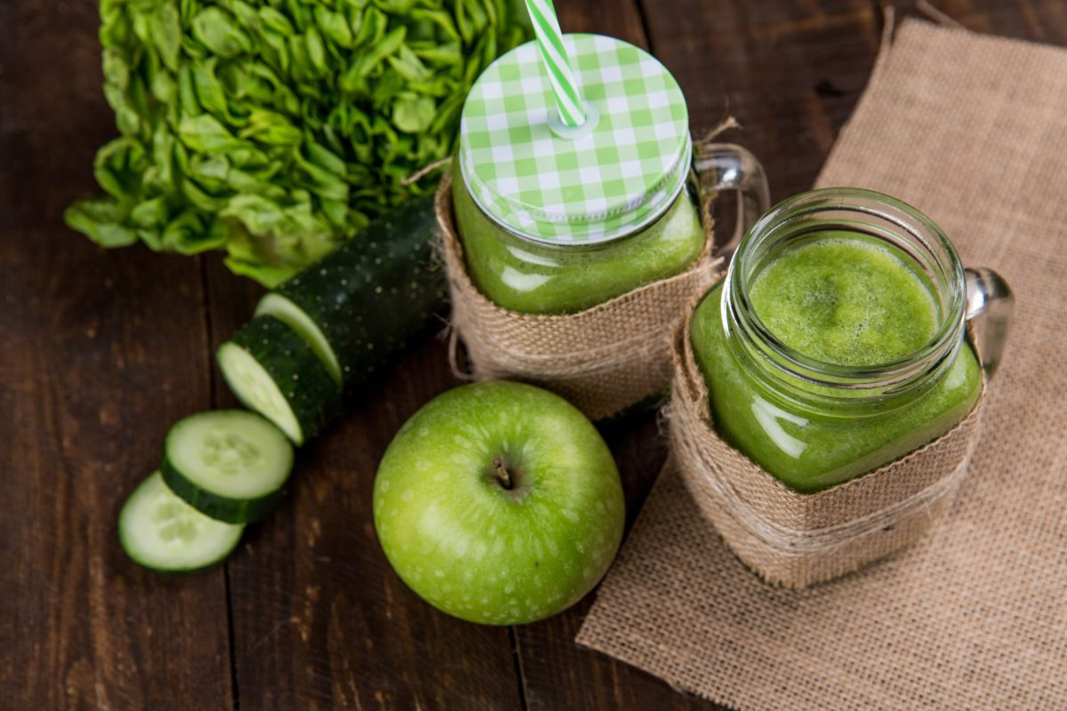 green apple smoothie in a glass with a straw and cucumber