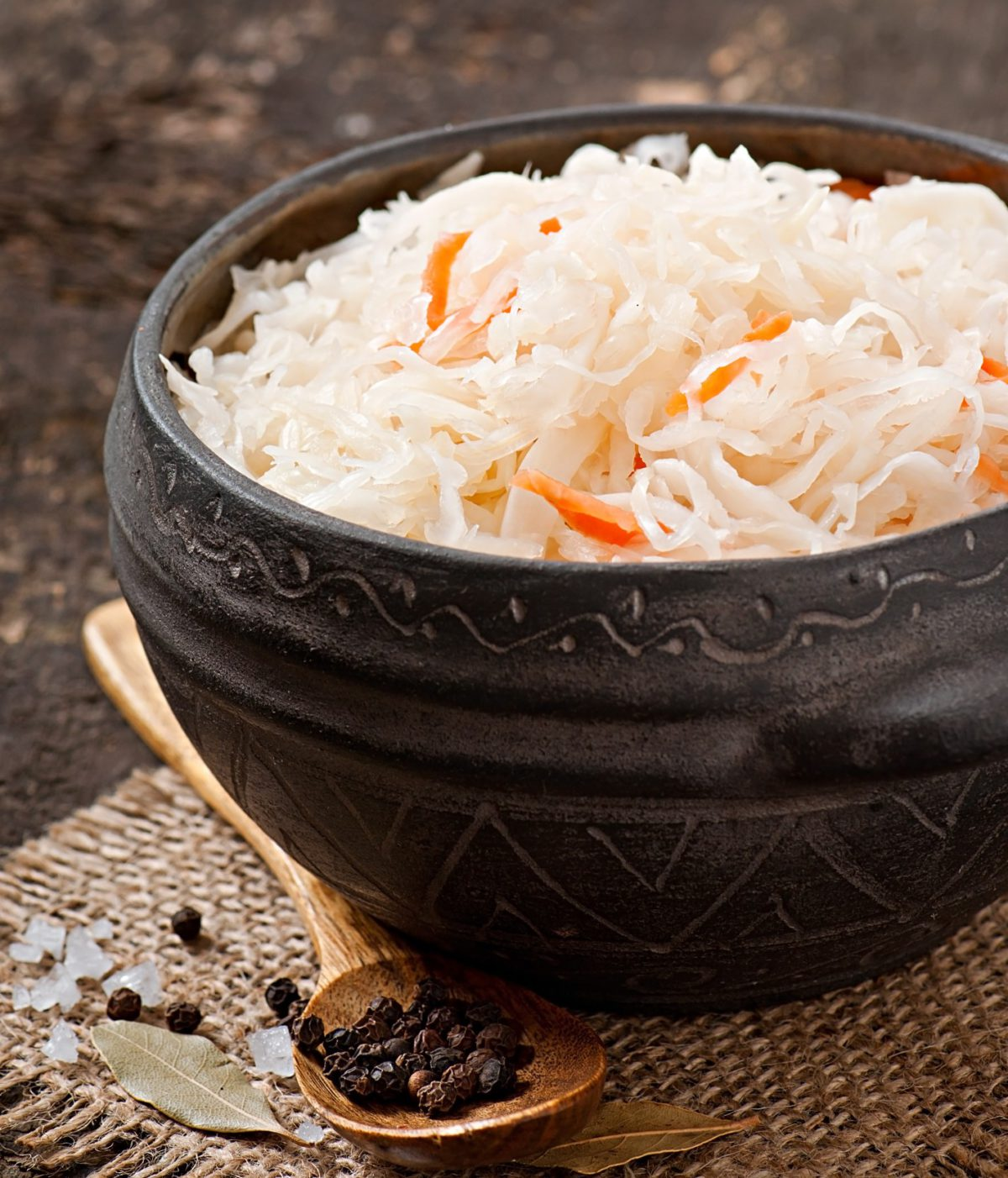 Coleslaw with carrot in a black bowl and a spoon